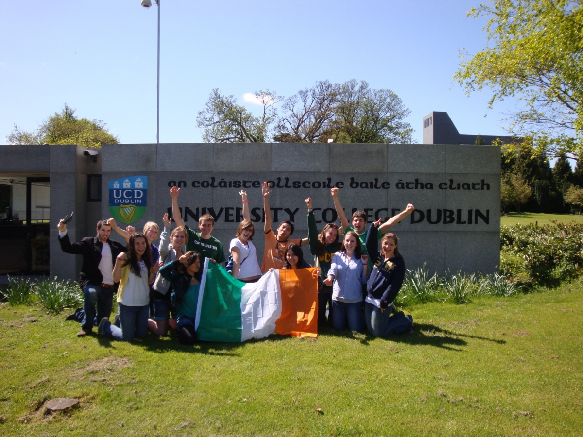 University College Dublin Study Abroad Students holding Irish flag in front of university sign
