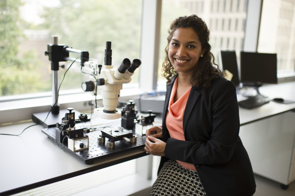 Dr. Saniya LeBlanc in front of microscope and other equipment